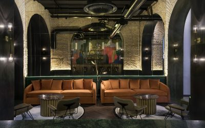 La lobby bar dell'Hotel Chapter, con divani arancioni e bancone in ottone