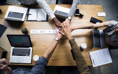 Team building in ufficio, mani che si incontrano intorno a una scrivania
