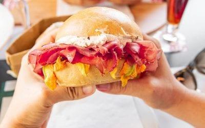 Un panino ripieno di Panino Giusto, stretto tra due mani, prima di essere addentato