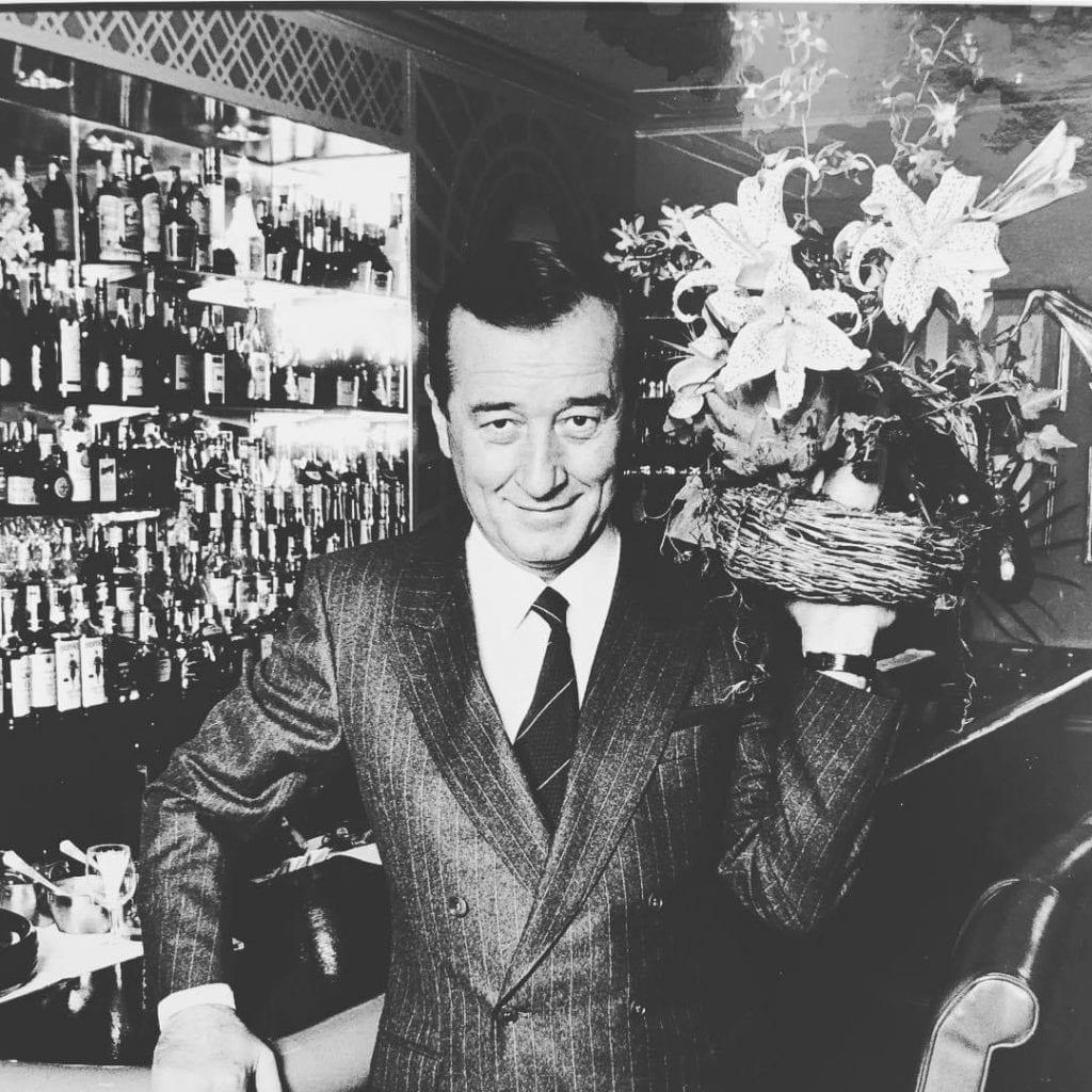 foto in bianco e nero di Sirio Maccioni al banco del bar