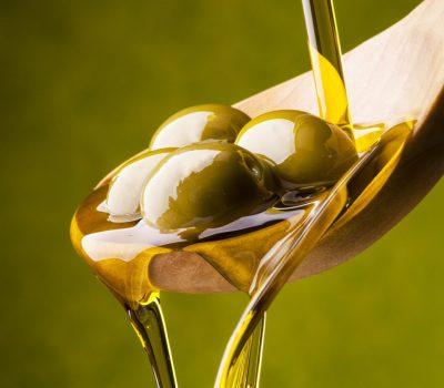 olio di oliva versato su un cucchiaio in legno con olive