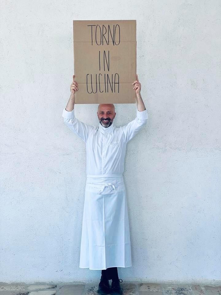 """Niko Romito in divisa da chef sorregge un cartello """"Torno in cucina"""""""