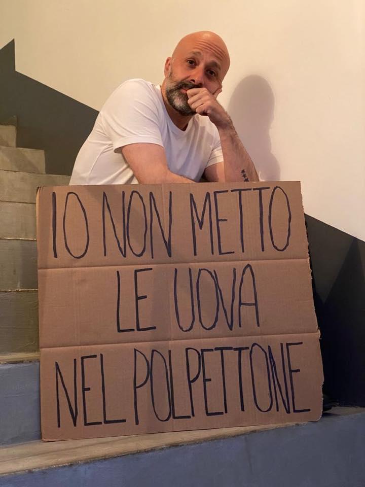 Niko Romito seduto sulle scale con cartello