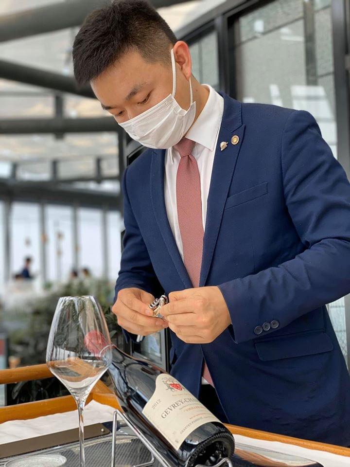 Un sommelier al lavoro con mascherina in un ristorante di Shangai