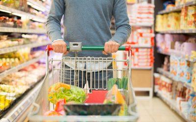 Un uomo si muove col carrello tra gli scaffali del supermercato