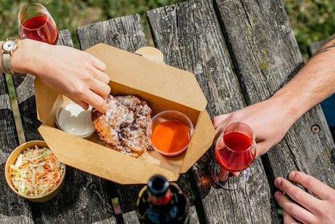 Pollo fritto e vino su tavolo in legno in giardino
