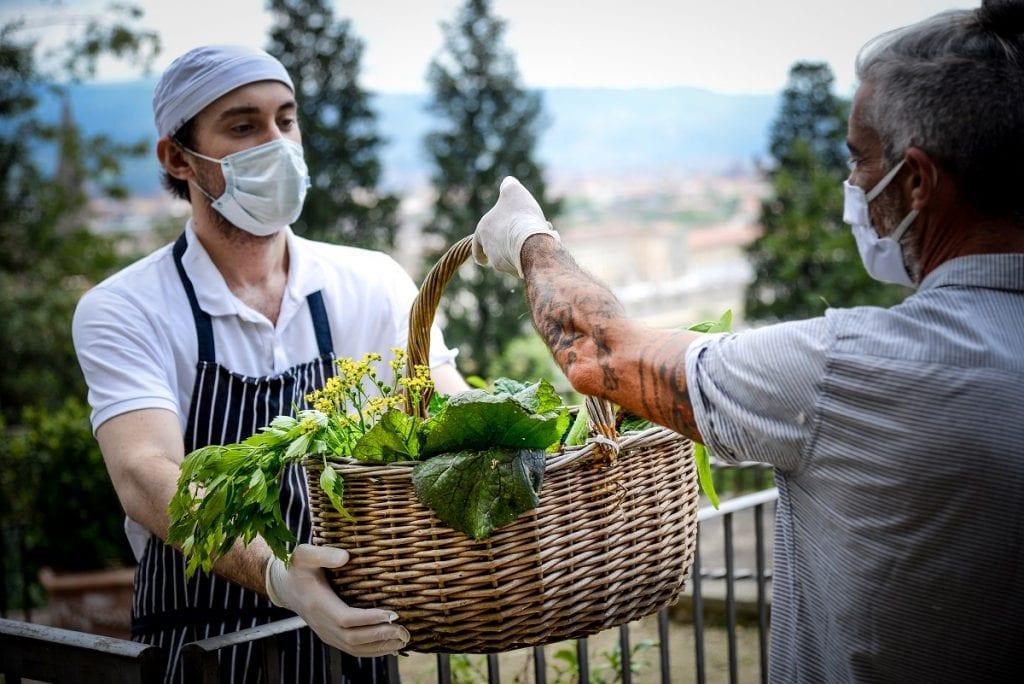 Scambio tra un fornitore di frutta e verdura e un ragazzo dello staff al ristorante