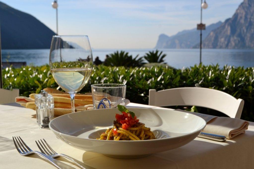 Un piatto di pasta al tavolo vista lago della terrazza di Torbole