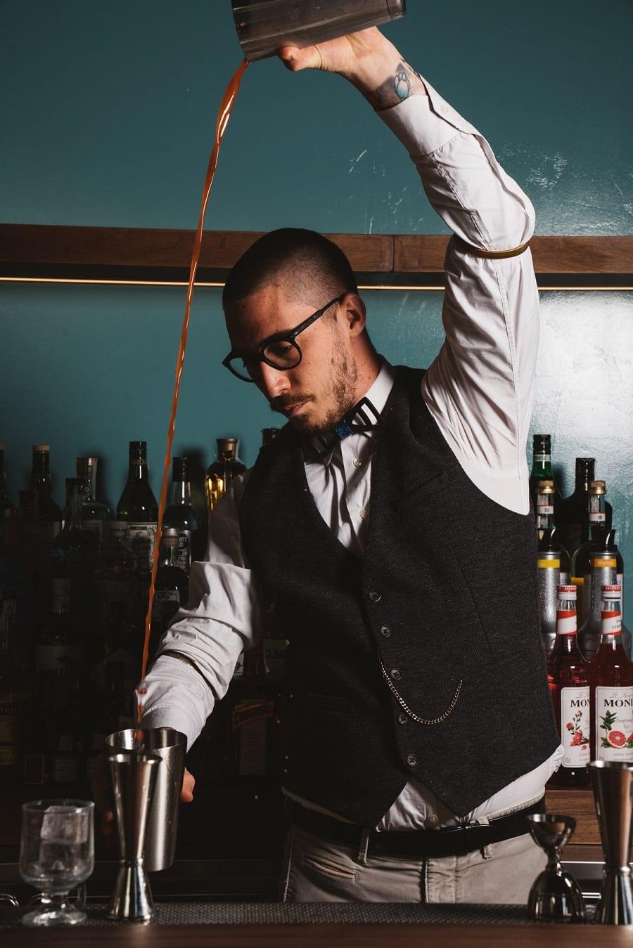 Il barman di Senza Pensieri al lavoro dietro al banco
