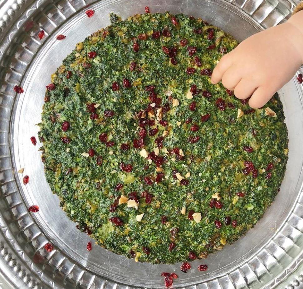 spezie ed erbe per frittata iraniana con mano di bimbo