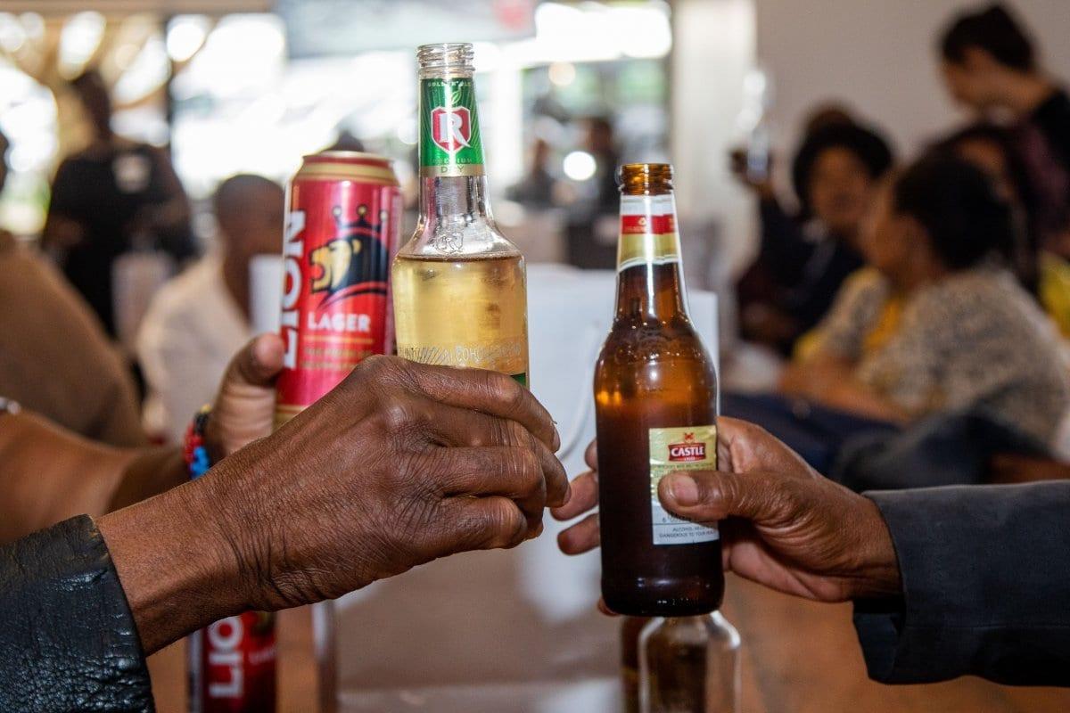 Tre uomini brindano con una bottiglia di birra al bar