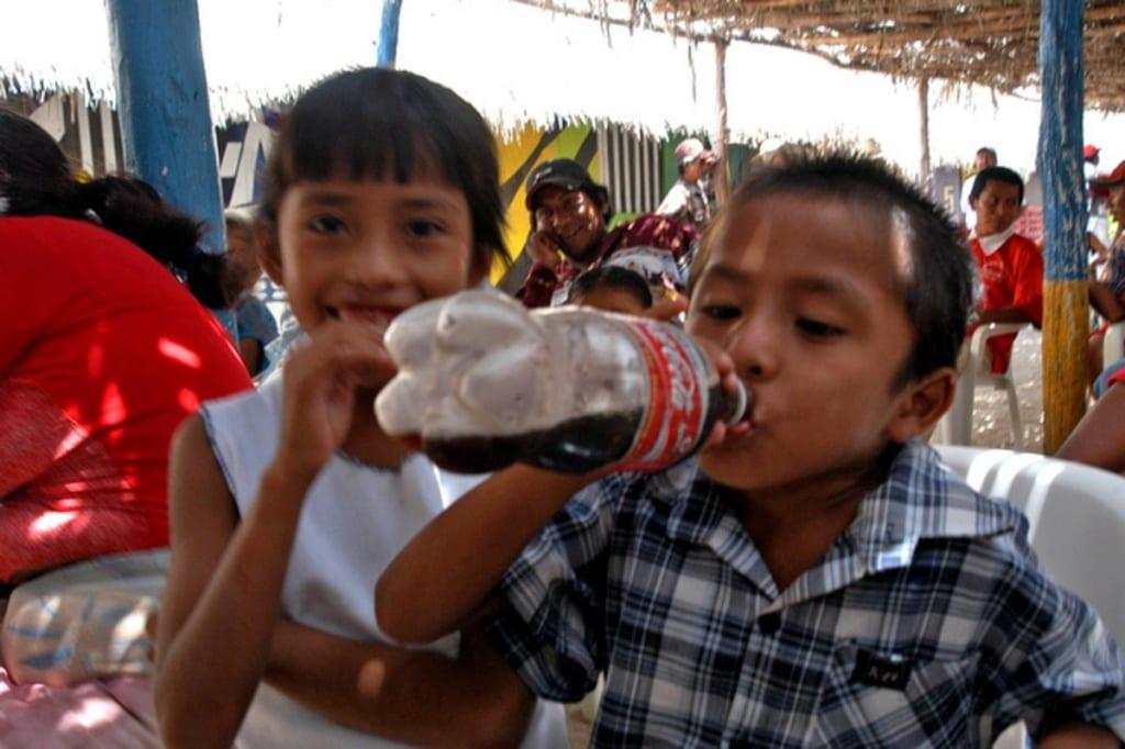 Bambini messicani bevono coca cola dalla bottiglia