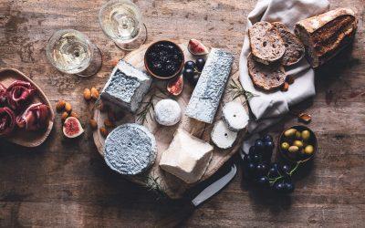 Formaggi, olive, pane e due calici di vino francese