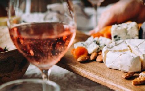 Tagliere di formaggi con calice di vino rosè
