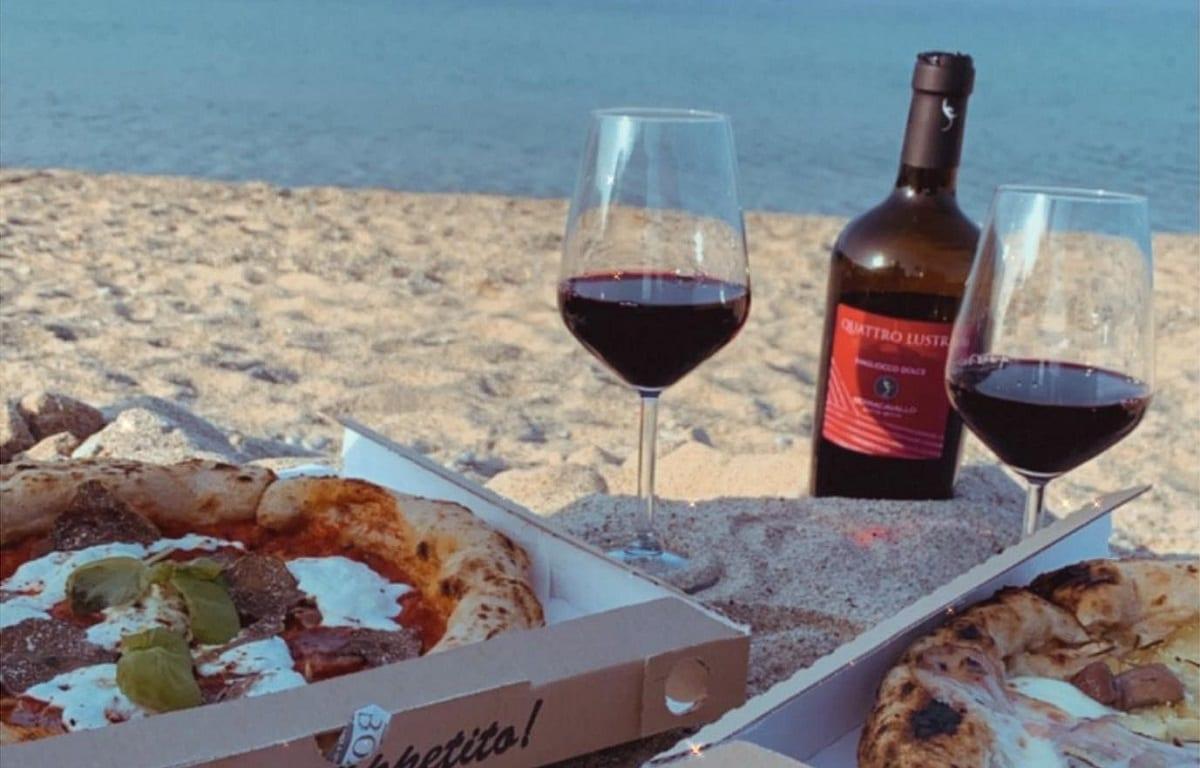 Pizze da asporto mangiate in spiaggia, con vino rosso