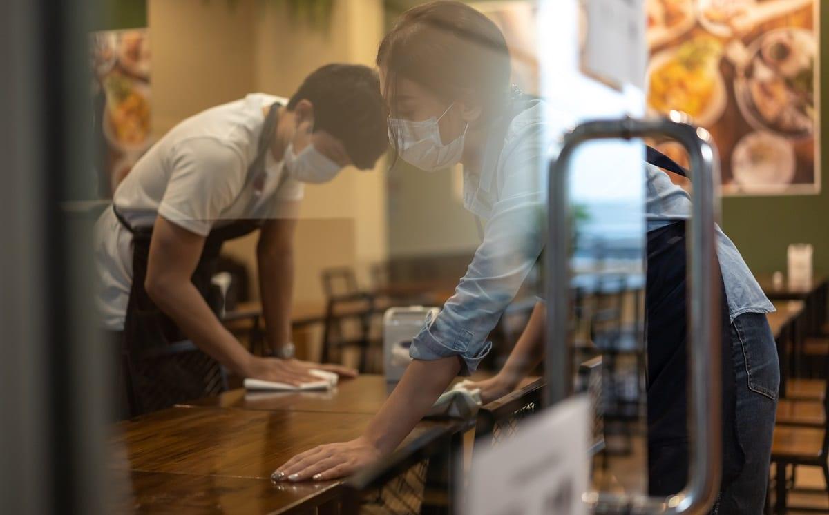 Camerieri al lavoro per sterilizzare i tavoli