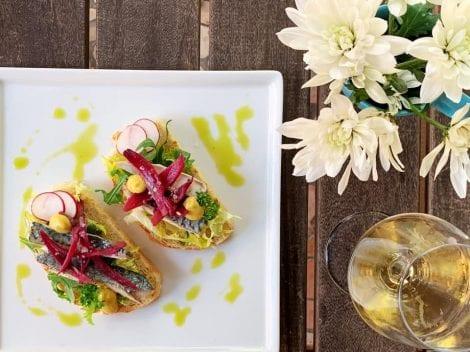 Crostini con sardoncini e cipolle e calice di vino bianco