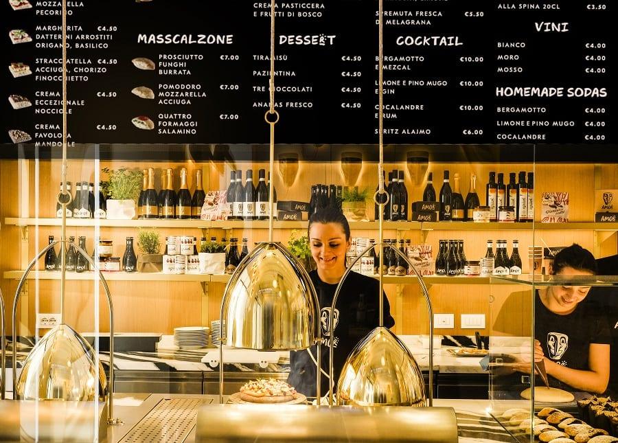 Il banco di Amor a Milano, con il menu su schermo nero e i forni a vapore brevettati da Alajmo