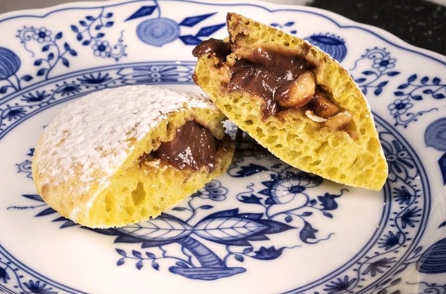 Due spicchi di calzone dolce al vapore con crema al cioccolato su piatto in porcellana con decori blu