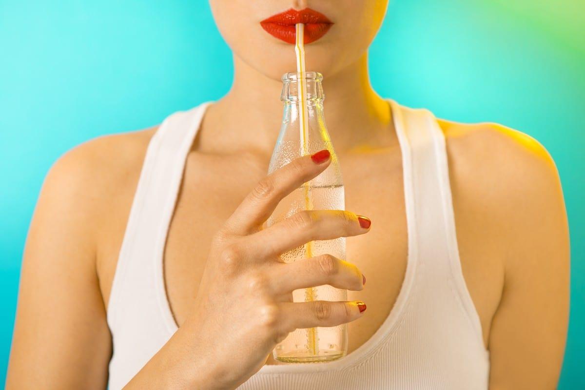 Donna con rossetto che beve dalla cannuccia