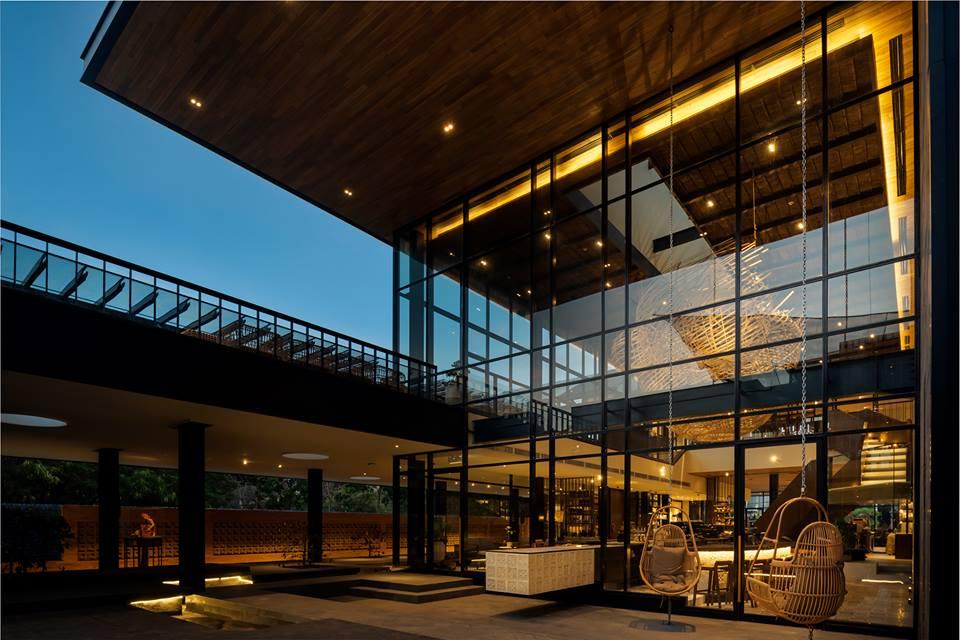 Lo store di Starbucks a Bali visto dall'esterno, con la grande parete vetrata, il tetto in legno, il cortile all'aperto, dopo il tramonto