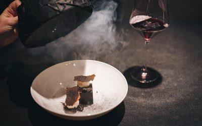 Un dessert di coda, con cloche nera che scopre l'affumicature e bicchiere di vino, su tavolo scuro