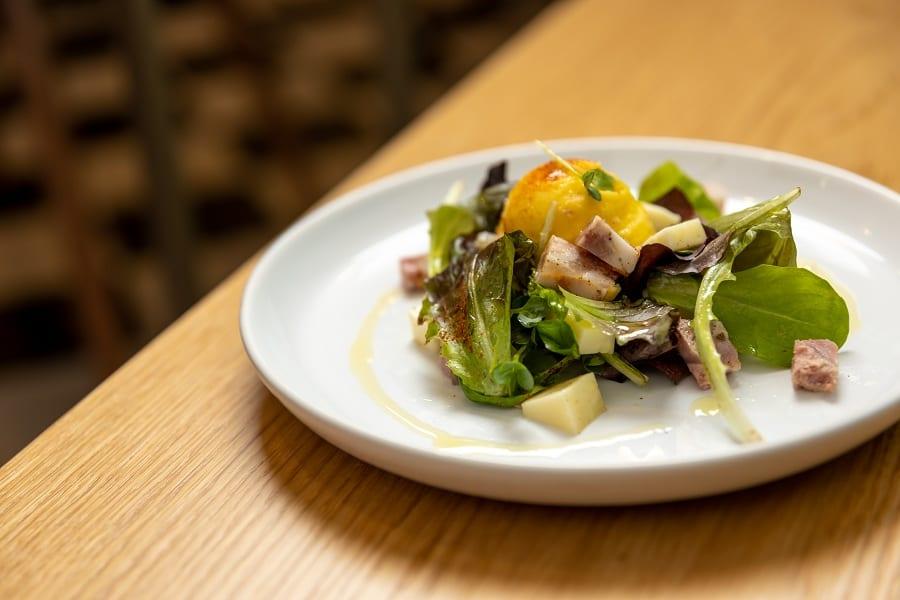 Un piatto con insalata, toma, coppa e gelato su tavolo in legno