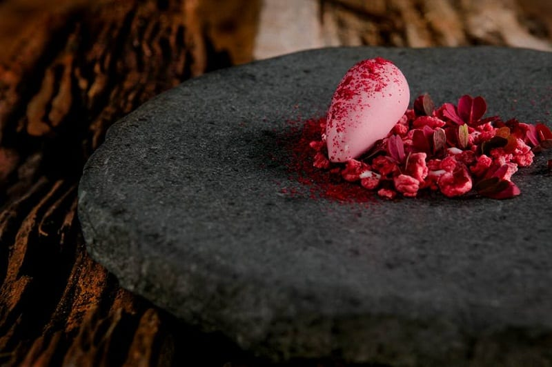 Un dolce del Boragò: gelato fucsia su piatto in pietra nera