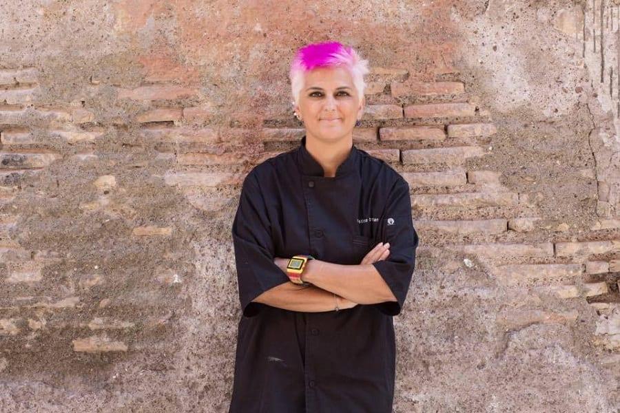 Ritratto di Cristina Bowerman con divisa nera da chef, su muro in mattoni rossi