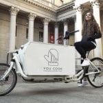 Una ragazza sulla cargo bike di You Cook, nel cortile interno di un palazzo storico