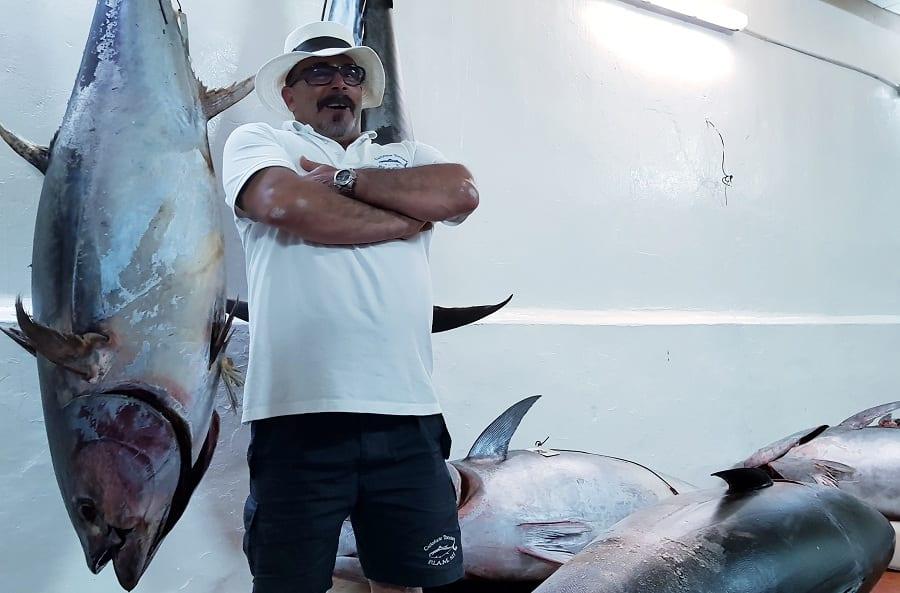 Il rais di Carloforte con un tonno appena pescato appeso per la coda