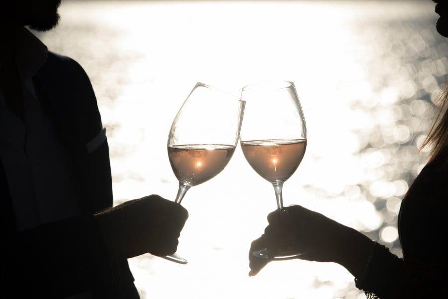 Due che brindano con calici di vino rosato