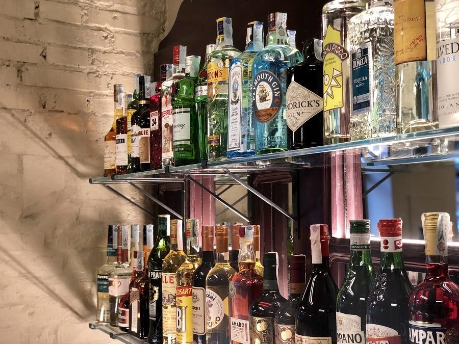 la bottigliera di Cresci, con le bottiglie di distillati e amari