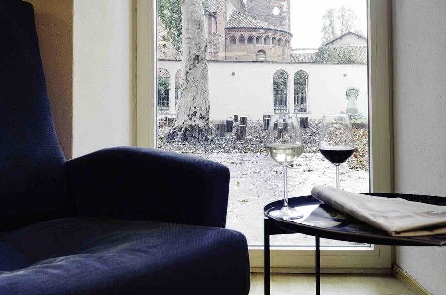 Due calici e la poltrona blu di Enoteca Naturale con vista sulla basilica di Sant'Eustorgio