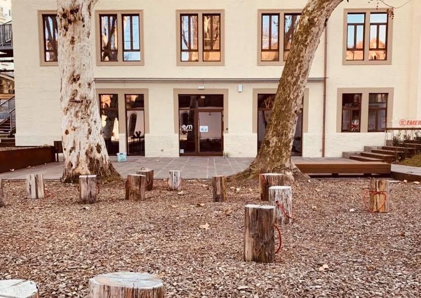 Il cortile dell'Enoteca Naturale con i ceppi in legno per sedersi e la facciata sullo sfondo