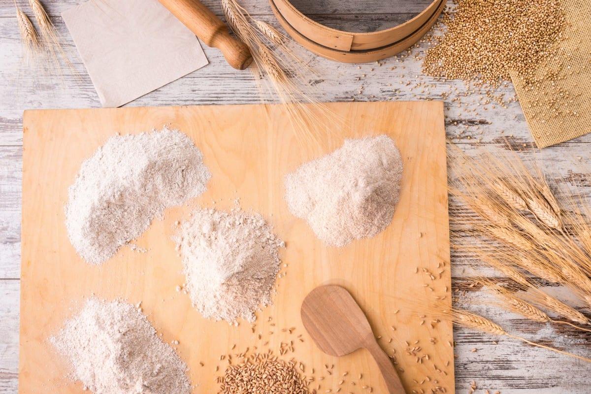 Farine integrali diverse sull'asse di legno con chicchi e spighe, setaccio e mattarello