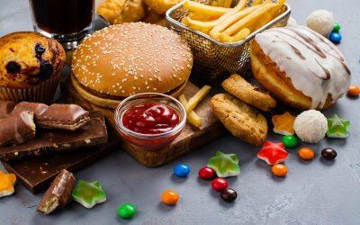 Cibo da fast food: un panino con hamburger, salsa ketchup, patatine fritte, caramelle gommose, cioccolato, cookies, muffin ai mirtilli, coca cola