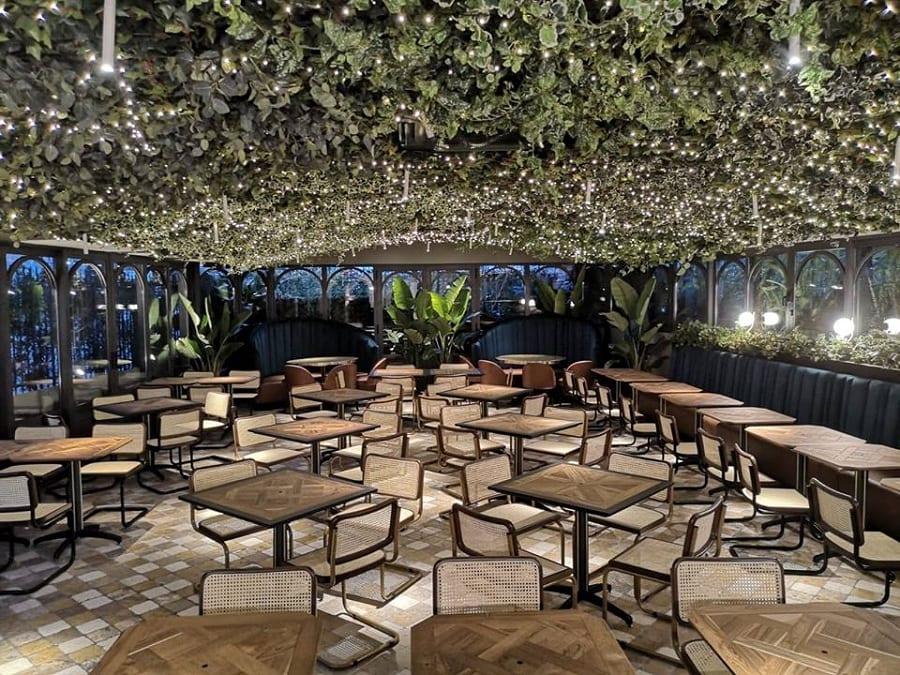 La veranda della Focacceria Manuelina con giardino sospeso, tavoli in legno e divanetti blu