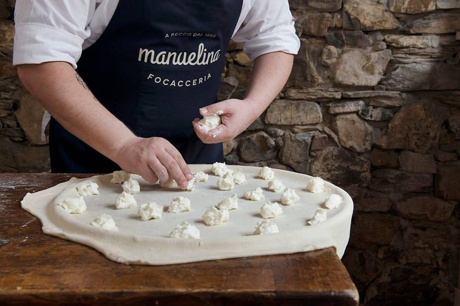 La preparazione della focaccia di Recco, con i fiocchi di stracchino disposti sulla sfoglia di pasta da un cuoco di Manuelina