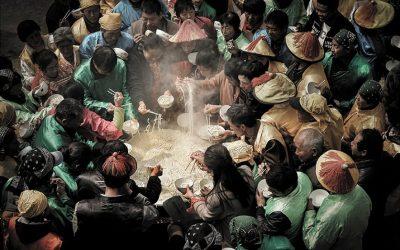 La spaghettata rituale in un villaggio cinese, in abiti tradizionali intorno a un calderone di noodle