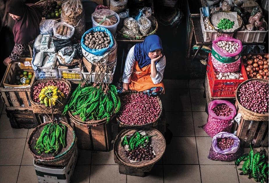 Donna islamica che vende frutta e verdura al mercato