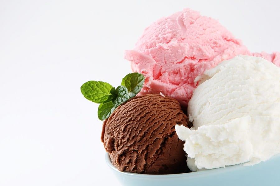Una coppa di gelato a tre gusti, fragola, cioccolato, vaniglia, con foglia di menta