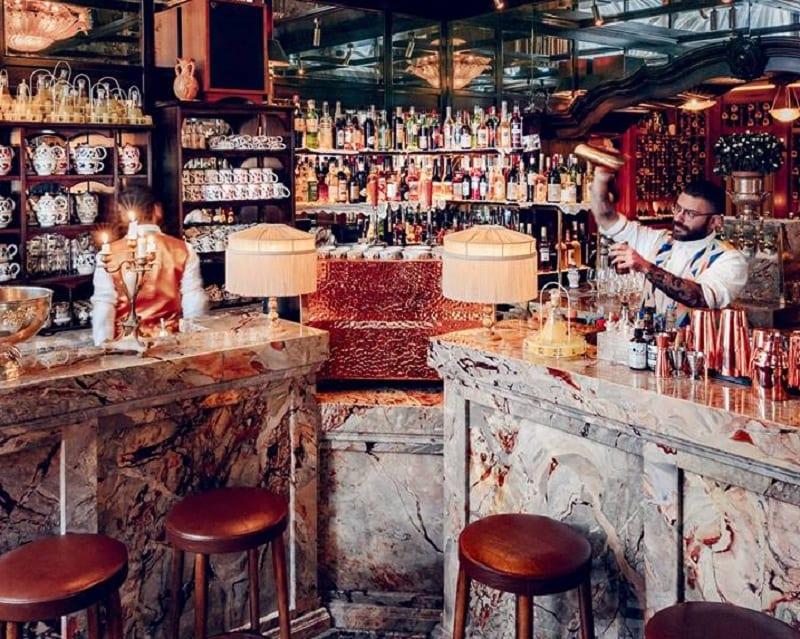 Il bar con bnachi in marmo di Carrara, sgabelli imbottiti, bottigliera a parete e soffitto specchiato, con du barman intenti a miscelare