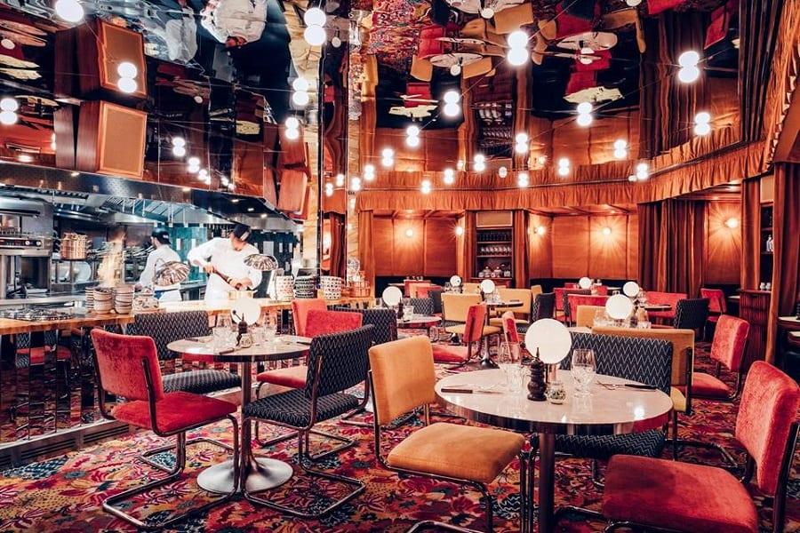 La sala di Gloria a Londra, con moquette rossa decorata, tavoli nudi, punti luce, soffitto specchiato, cucina a vista