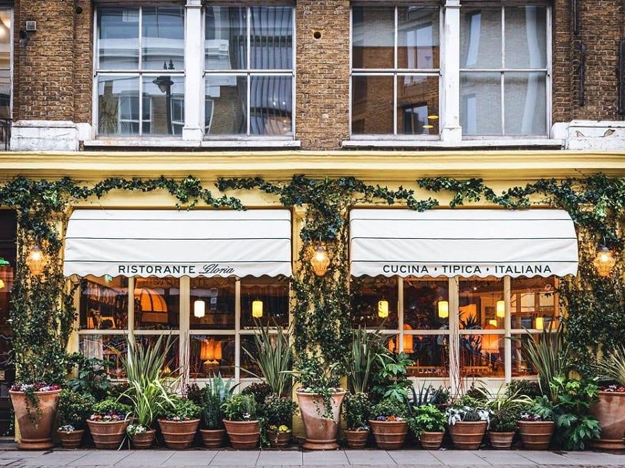 Le vetrine su strada di Gloria, con vasi di piante e tende bianche