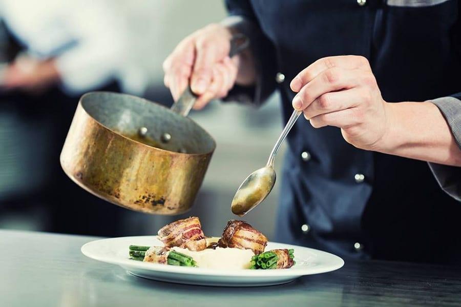 Un cuoco in divisa nera termina il piatto con la salsa presa dalla pentola
