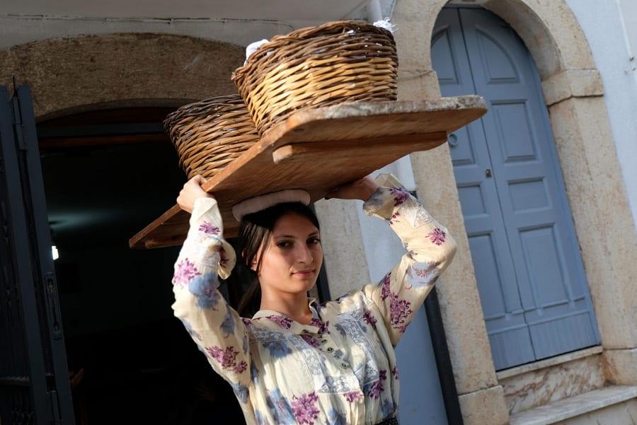 Una ragazza vestita tradizionale con cesti di vimini sulla testa a Grani Futuri 2019