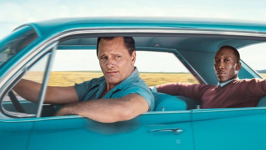 La locandina del film Green Book, con Viggo Mortensen alla guida di una macchina azzurra