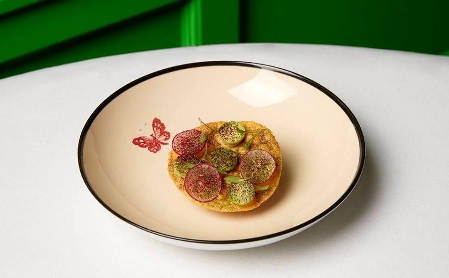 La tostada di Gucci Osteria, su piatto in porcellana con farfalla dipinta