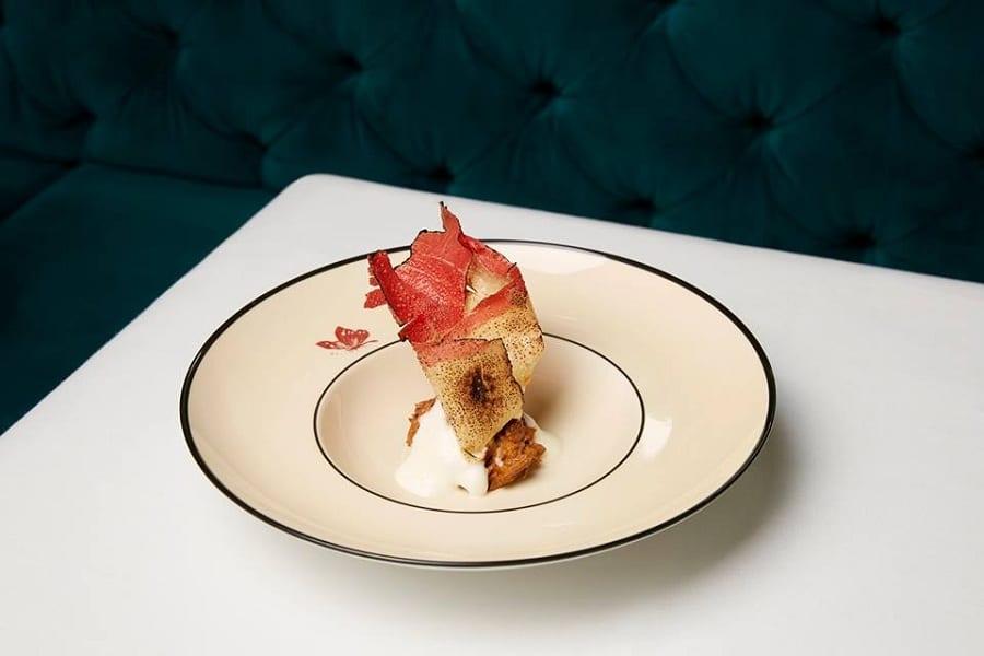 Ricordo di una lasagna croccante, piatto in porcellana su tavolo bianco